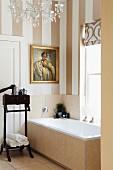 Antique, dark wood valet stand next to bathtub below window in bathroom with striped wallpaper