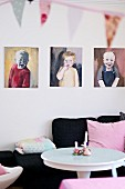 Portrait paintings of children above black sofa with pink scatter cushion and white table