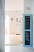 Writing on blackboard in pale blue, cupboard door frame next to doorway leading to dining room with view of white, old-fashioned dresser