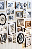 Gallery of retro-style family photos in various frames on white wooden wall