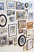 Sammlung von Familienfotos in verschiedenen Rahmen an weisser Holzwand mit nostalgischem Flair