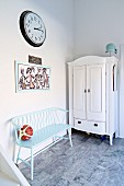 Wooden bench painted pastel blue next to white farmhouse cupboard