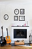 Guitars next to open fireplace below framed family photos