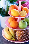 Verschiedene Früchte auf rosafarbener Etagere