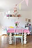 Massiver, weisser Esstisch mit gedrechselten Beinen mit rosa-weiss gepunkteter Tischdecke im Esszimmer mit pastellfarbener Wimpelgirlande dekoriert