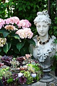 Pink hydrangea next to bust of woman and large wreath of succulents