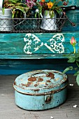 Blue potting table with wire basket and rusty metal tin