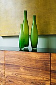 Set of three green vases on sideboard with walnut front