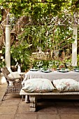 Set table on terrace below climber-covered pergola