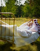 Child waking up in bed in meadow