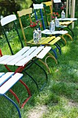 Row of vintage garden chairs with colourful metal frames