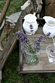 Lavender flowers in glass and china crockery on wooden table