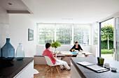 Mann und Frau am Esstisch vor Fensterfront mit halbgeöffneten Jalousien in offener Küche
