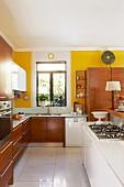 Offene Küche mit weisser Kochinsel und Einbauschränke aus Holz vor gelb getönter Wand