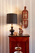 Table lamp with black lampshade and glass cover on cabinet below ethnic ornament on wall with white and grey stripes pattern