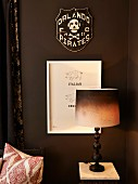 Table lamp with dip-dye-style lampshade in front of pictures on dark brown wall