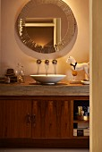 Fitted washstand with basin on concrete counter and wooden base cabinet below round mirror with decorative edge