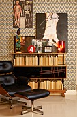 Classic Eames Lounge Chair with black leather cover and matching footstool in front of bookcase and artworks on wall with retro, graphic-patterned wallpaper