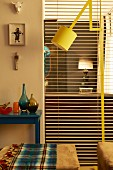 Yellow, adjustable standard lamp between ottomans and full-length, open louver blind with view into adjacent room