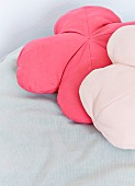 Two flower-shaped scatter cushions in shades of pastel pink