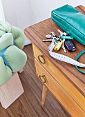 Key chair and turquoise handbag on fifties wooden cabinet