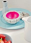 Betonschale - innen Magenta - mit Vase auf hellblauem Porzellanteller; Milchkännchen und Erdbeerschale im Vordergrund