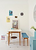 Youthful dining area with delicate, designer furnishings and small posters on wall