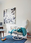 Pale blue blanket on white swivel armchair and modern artwork on wall