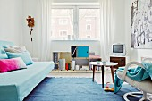 Youthful interior in shades of blue with scatter cushions on sofa bed, cuckoo clock and delicate designer furniture