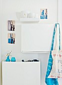 Blue Danish vases on white shoe cabinet and artistic postcards on wall