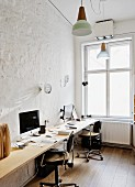 Office with long desk for two people and vintage desk chairs against wall in minimalist interior with traditional ambiance