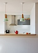Kitchen counter with wooden worksurface below row of pendant lamps in open-plan, minimalist kitchen