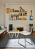 Classic wire chair and coffee table on rug in front of shelf and guitar hung on wall
