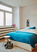 Blue blanket on French bed with wooden swivel stool at foot in minimalist bedroom