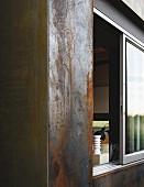 Cortenstahl-Fassade eines Wohnhauses mit Blick durch ein Schiebefenster nach innen