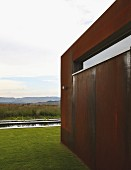 Minimalist house with Corten steel facade in untouched, wide natural landscape