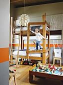 Junge am Hochbett kletternd; orangefarbene Wandstreifen und Aststrukturen an der Wand