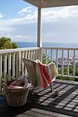 Handtuch über hellem Korbstuhl und Weidenkorb auf sonnigem Terrassenboden aus Holz mit Meerblick
