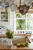 Tropical plants in white china jug on kitchen counter below utensils suspended from rack in rustic kitchen