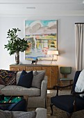 Grey couch in front of vase of foliage and table lamp on sideboard below modern landscape painting