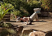 Sunny spot for relaxing in garden - woman and cat lying on wooden deck