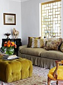 Ottoman with lime green cover and colourful bouquet in vase opposite sofa below window with wooden lattice framework
