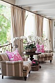 Armchairs with striped upholstery in grey and white either side of round table in front of gathered curtains and half-height grilles leading to veranda