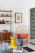 Yellow, zigzag stool and chair with high, curved backrest and radiating struts next to shelving unit with fifties-style base cabinet