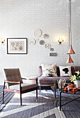Fifties armchair and grey sofa around coffee table below pendant lamps with copper-coloured lampshades in loft-style interior with decorative wall plates on whitewashed brick wall