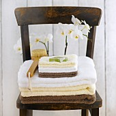 Towels, soap and bath brush in front of orchid on wooden chair