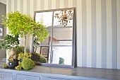 Mirror hand-crafted from old window frame with metal lattice on cabinet against striped wall