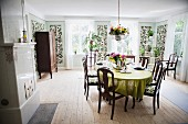 Dining room with dark wooden chairs around table and slim, floral panels on walls in rustic interior