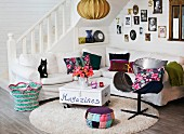 Colourful scatter cushions on white corner sofa and magazine box on castors used as coffee table; gallery of photos on wall and country-house staircase in background