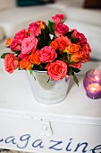 Vase of roses and tealight on trunk with lettering